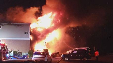 A fire engulfs part of an apartment complex