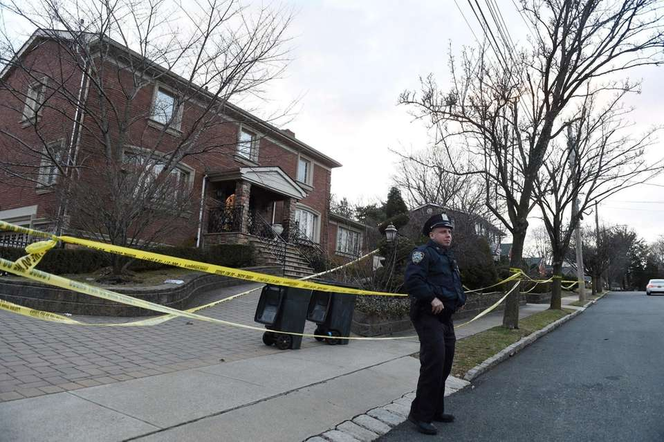 An NYPD officer safeguards the home of slain