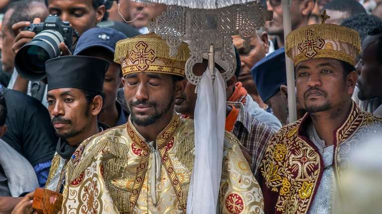 A priest cries during a mass funeral at