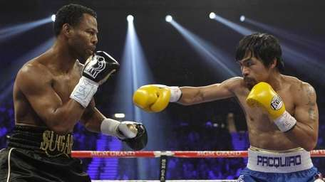 Shane Mosley, left, and Manny Pacquiao exchange punches