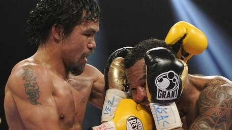 Manny Pacquiao, left, lands a punch against Shane