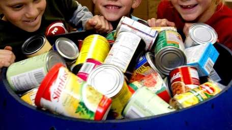 Young kids push a barrel of canned food