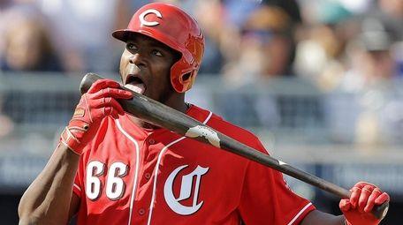 Cincinnati Reds' Yasiel Puig licks his bat during