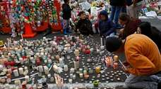 Students light candles as they gather for a