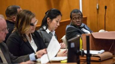 Chanel Lewis, right, sits with his defense team
