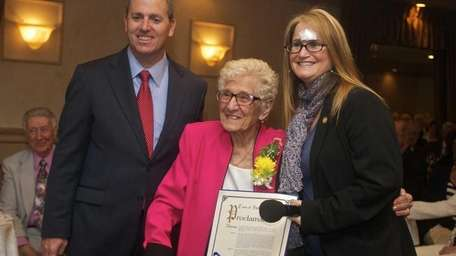 Sophie Sarro, 98, center, of Huntington Station receives