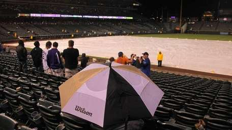 Fans take cover under an umbrella as the