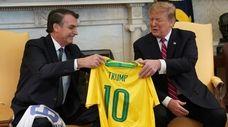 Brazilian President Jair Bolsonaro presents President Donald Trump