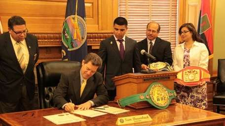 Governor Sam Brownback signs proclamation while (left to