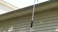 Cleaning gutters using a gutter wand connected to
