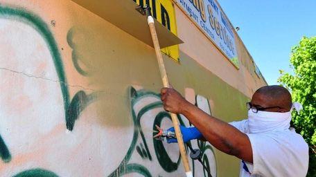 Raymed Neptune of CitySolve cleans up graffiti on