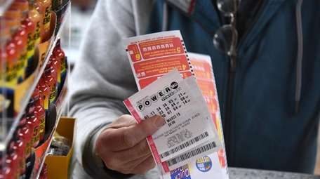 A customer holds his lottery ticket at Route