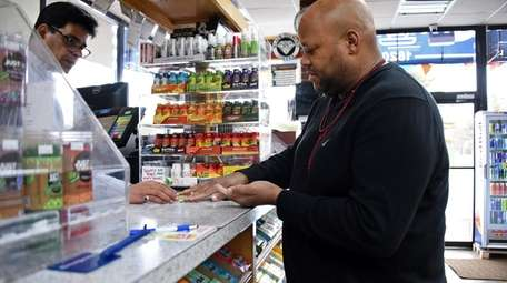 Jay Thompson of Westbury buys Powerball tickets at