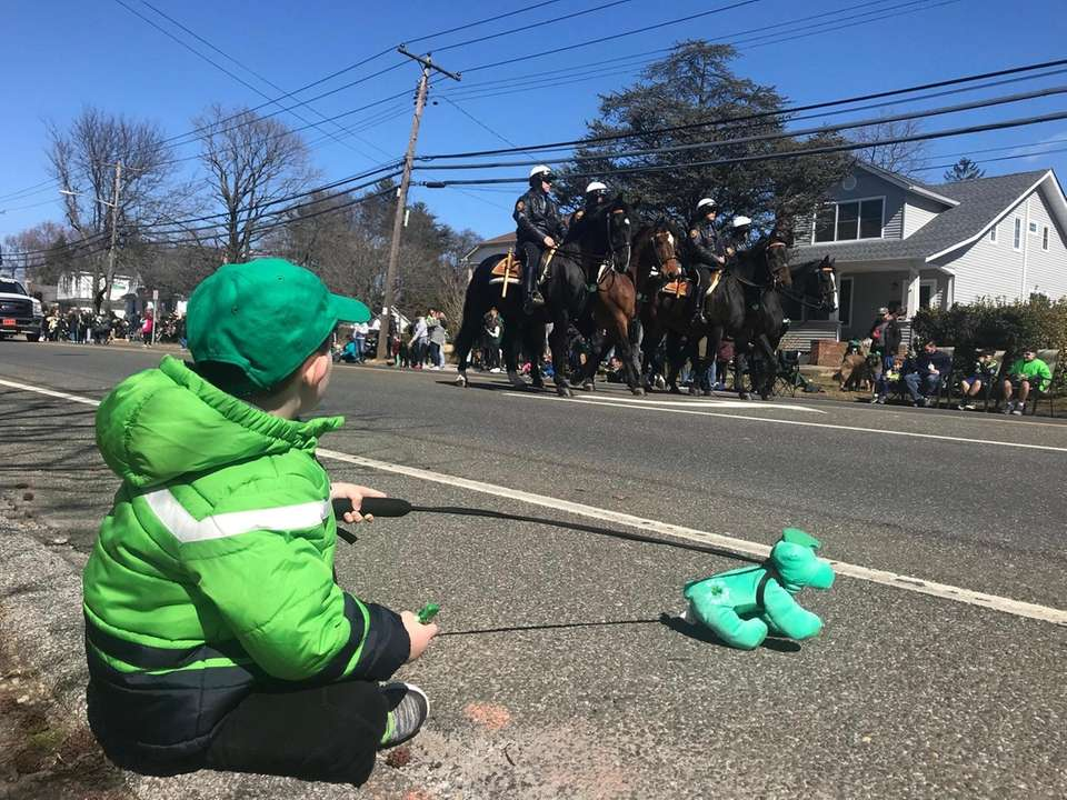 A young parade attendee sits on the sidelines