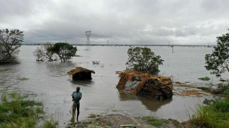 A man stands in floodwaters following cyclone-force winds