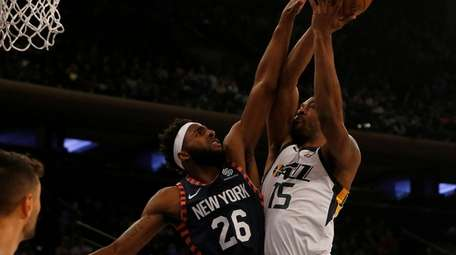 Mithcell Robinson defends Utah's Derrick Favors at Madison