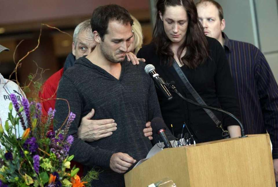 Aaron Boogaard, left, breaks down while speaking about
