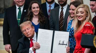 President Donald Trump, with conservative student activists, signs