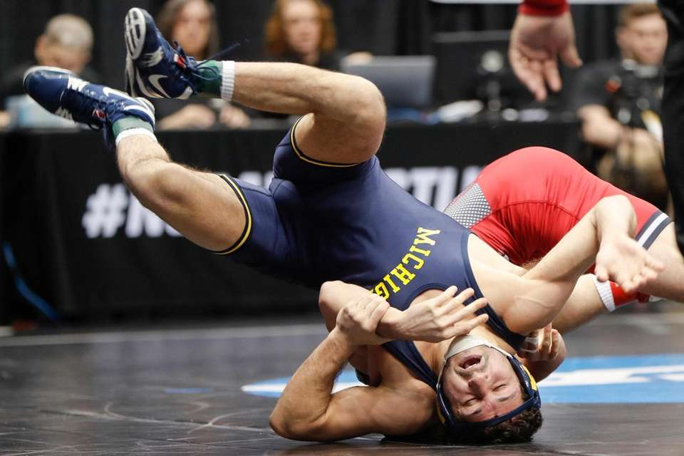 Michigan's Malik Amine, left, gets turned over by