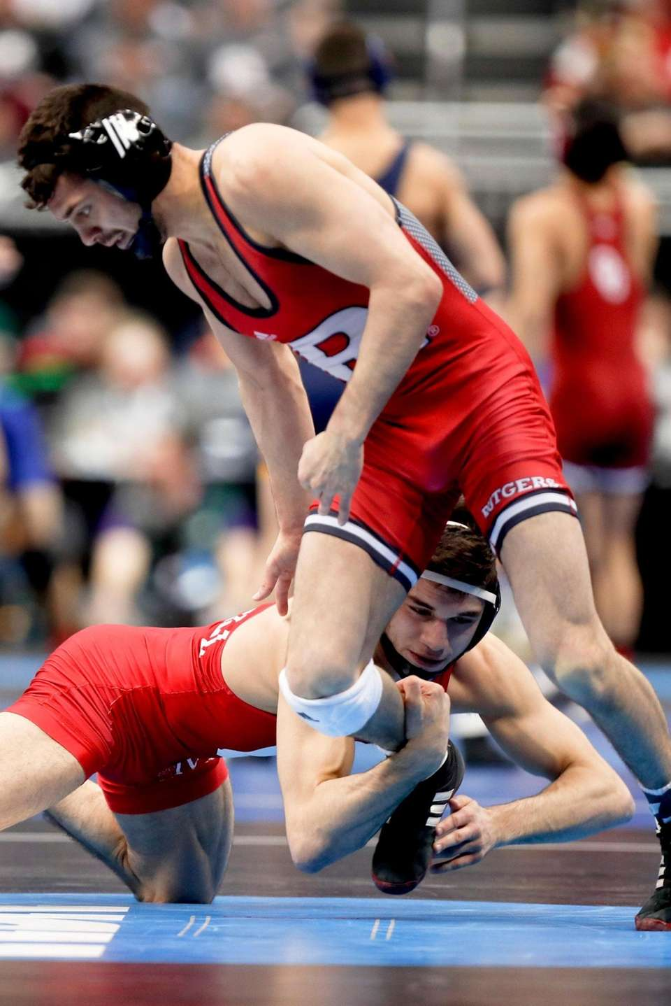 Cornell's Yianni Diakomihalis, bottom, grabs the leg of