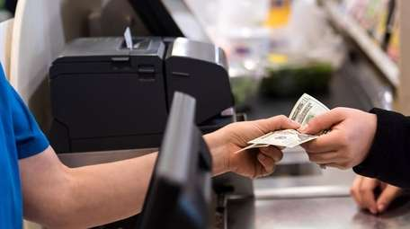 Woman giving cash when paying at a supermarket.