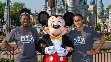 Mickey Mouse, welcomes Kaiya Simmons, left, and Tianna