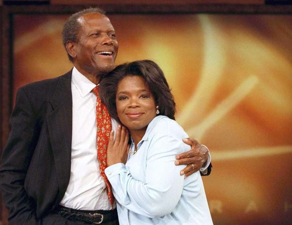 Talk-show host Oprah Winfrey is embraced by actor