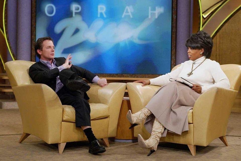 Actor Michael J. Fox demonstrates to Oprah Winfrey