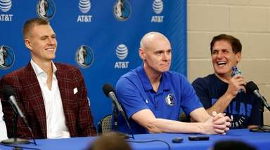 Mavericks forward Kristaps Porzingis, left, laughs after responding
