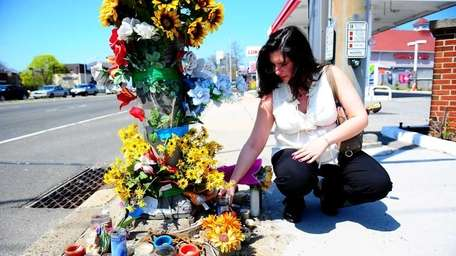 Sandi Vega tends a makeshift memorial for her
