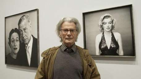 Richard Avedon poses with his photographs of Marilyn