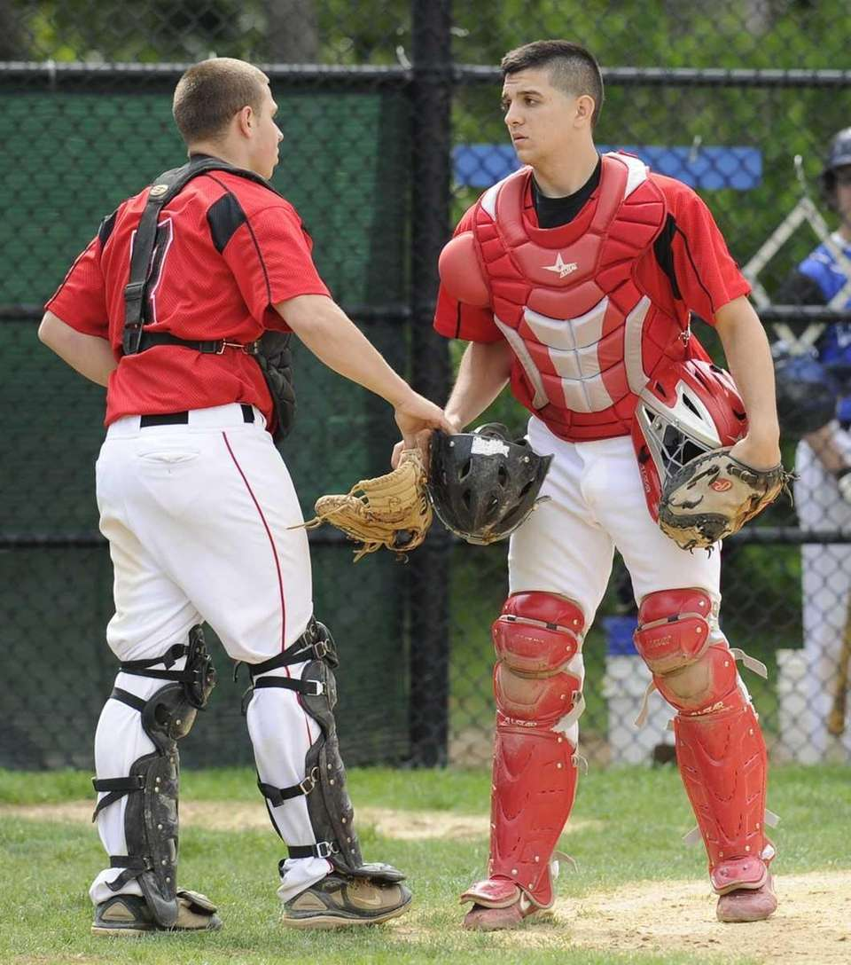Newfield catcher Dan Merola, left, is replaced by