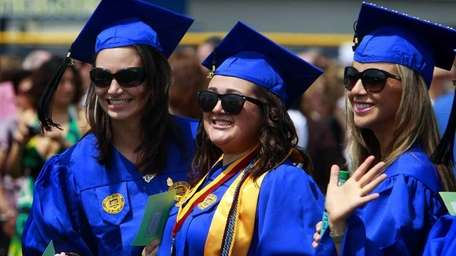 Graduates pose for pictures at the 49th commencement