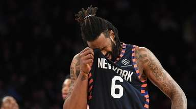 Knicks center DeAndre Jordan wipes his face on