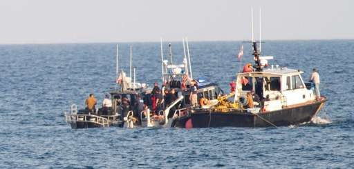 Police and recovery boats near where plane wreckage