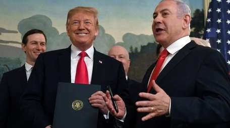 President Donald Trump smiles as he holds a