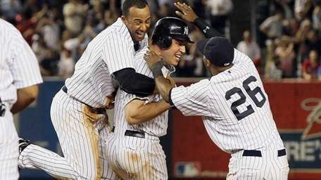 Yankees teammates mob Mark Teixeira after he delivered