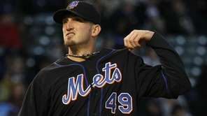 Mets starting pitcher Jonathon Niese tugs at his