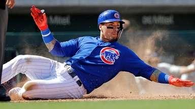 Chicago Cubs' Javier Baez slides safely across home