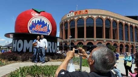 Fans take photographs outside Citi Field. (May 8,
