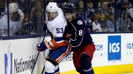 Blue Jackets defenseman Zach Werenski, right, checks Islanders