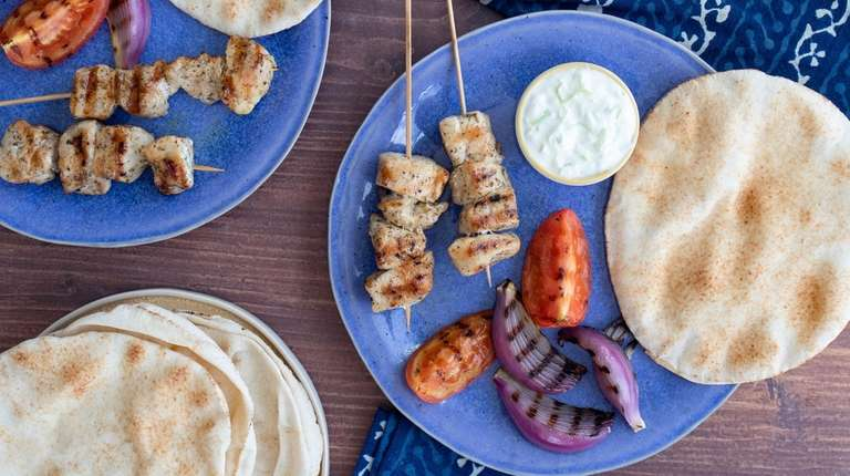 Seasoned chicken kebabs, onion and tomato are cooked