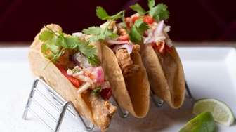 Crunchy barramundi fish tacos are served in crisp