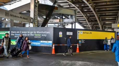 Passengers pass the area at Jamaica Station on