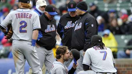 Mets starting pitcher R.A. Dickey, center, sits on