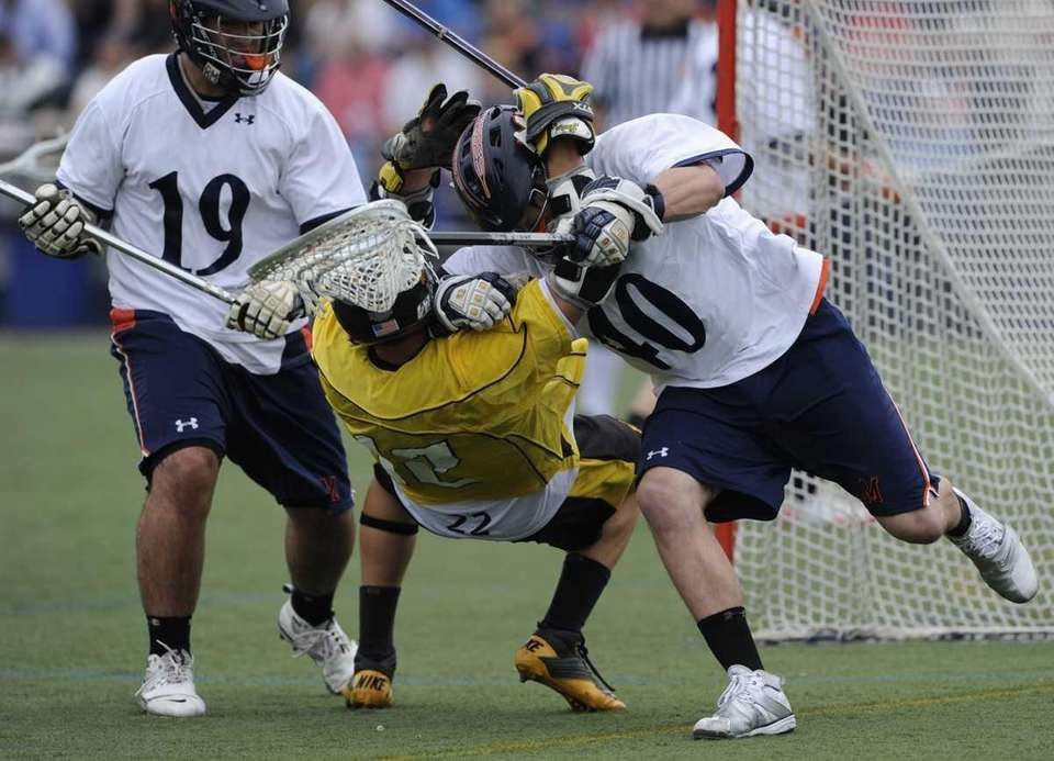 Manhasset goal keeper Frank Morelli, right, battles for