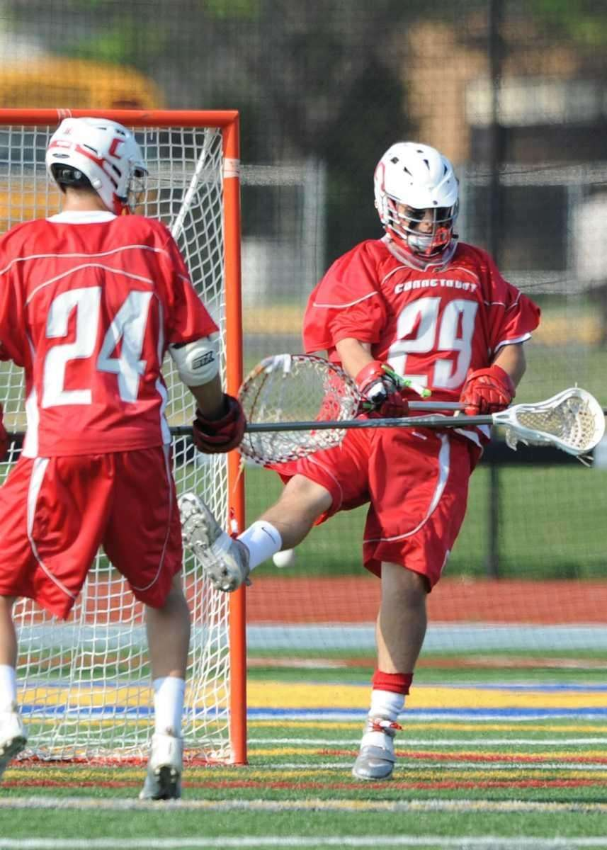 Connetquot's Zach Oliveri (29) deflects the shot off