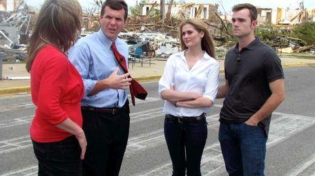 Tuscaloosa Mayor Walt Maddox, second from left, talks