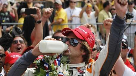 IndyCar driver Dan Wheldon, of England, drinks from