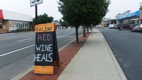 The sign in front of Salumi Tapas &